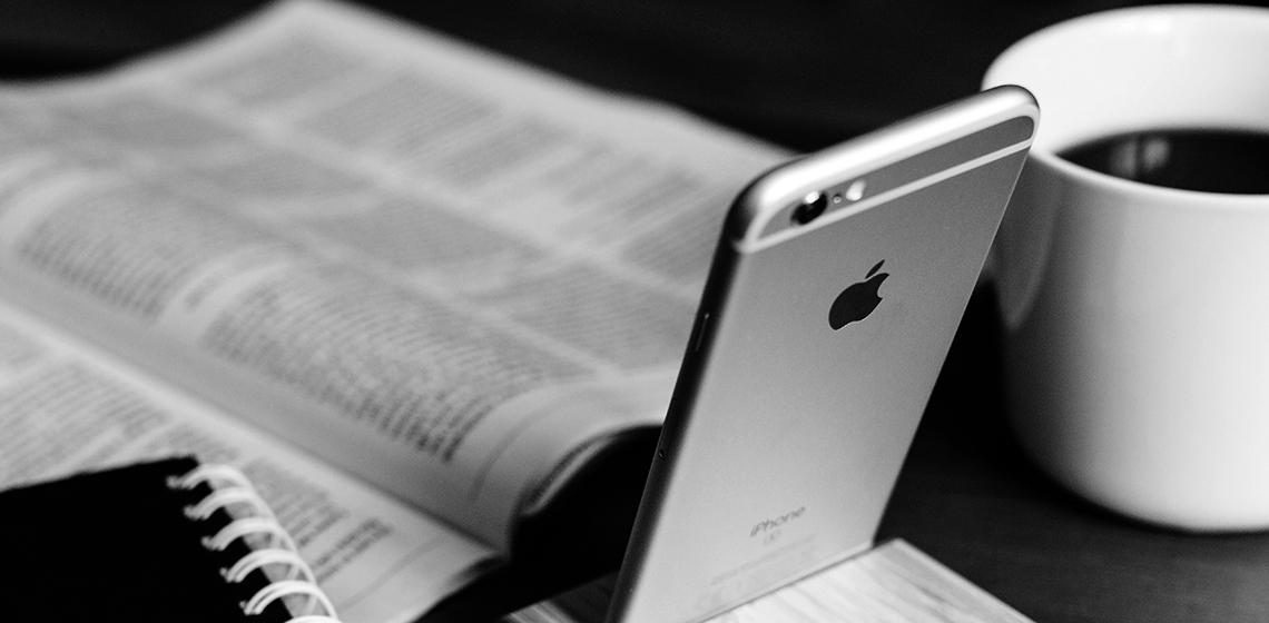 Ein Handy mit Mitarbeiter-App und eine Mitarbeiterzeitschrift